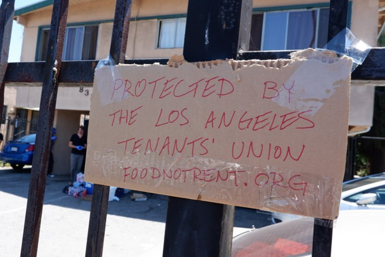 "a sign on a gate that says ""protected by the los angeles tenants union:"